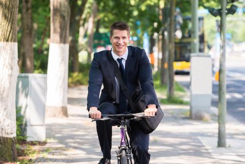 Portrait Of Happy Young Male Businessman Riding Bicycle